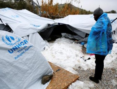 A migrant is covered with a plastic cover to protect from low temperatures as snow lays next to tents provided by the UNHCR at the refugee camp of Moria on the Greek island of Lesbos, January 10, 2017. Petros Tsakmakis/Intimenews via REUTERS