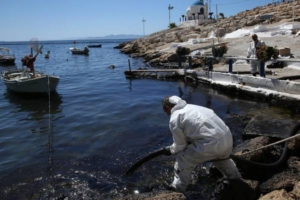 epa06202215 Workers of a clean-up crew struggle to remove an oil spill from a beach of the coastal zone of Athens, Greece, 13 September 2017. The small tanker 'Agia Zoni II' sank on 10 September, while anchored off the coast of Salamina, near Greece's main port of Piraeus, with a cargo of 2,200 tons of fuel oil and 370 tons of marine gas oil.  EPA/ORESTIS PANAGIOTOU