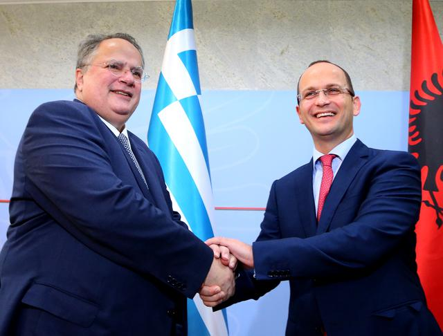 Greek Foreign Minister Nikos Kotzias, left, shakes hands with Albanian Minister of Foreign Affairs Ditmir Bushati prior to their meeting in Tirana, Wednesday, July 15, 2015. (AP Photo/Hektor Pustina)