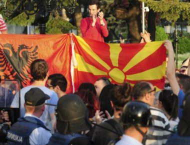 epa04734524 Protestors hold Macedonian and Albanian flag in front of the cordon of special police forces who are guarding the government building during an anti-government protest in Skopje, the Former Yugoslav Republic of Macedonia, 05 May 2015. Protesters gathered after opposition leader Zoran Zaev leaked surveillance conversations that involve government officials discussing the cover up of details important in the murder of Martin Neskovski in 2011. Neskovski was killed by a member of the special police forces and he was sentenced to 14 years of imprisonment.  EPA/IVANA BATEV