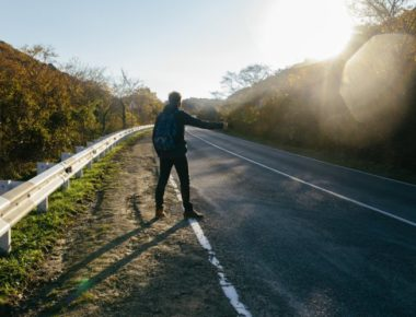 Man hitchhiking on a country road. Traveler showing thumb up on for hitchhiking during road trip. Adventure and tourism concept.n; Shutterstock ID 530155432; Purchase Order: -