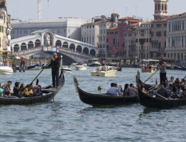 Tourists tour the Grand Canal on traditional Gondola Venetian boats, in Venice, Italy, Sunday, Sept. 28, 2014. (AP Photo/Andrew Medichini)