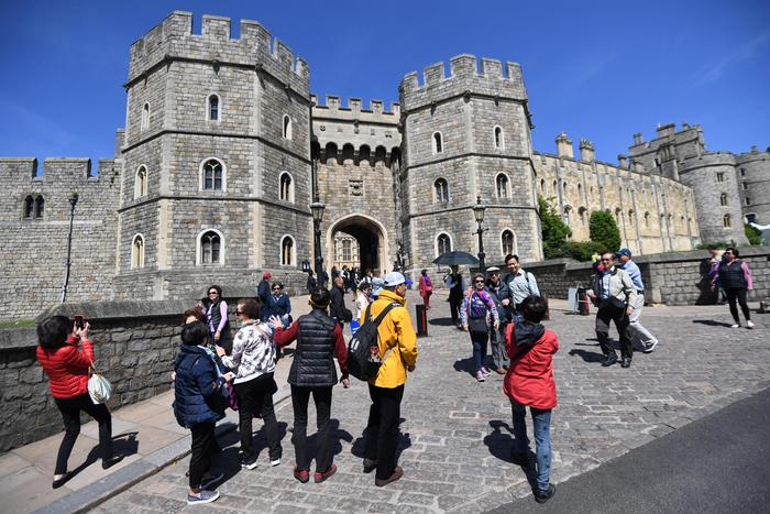 epa06736047 Tourists walk near Windsor Castle, in Windsor, Britain, 14 May 2018. Britain's Prince Harry and his fiancee Meghan Markle will marry at Windsor Castle on 19 May.  EPA/NEIL HALL