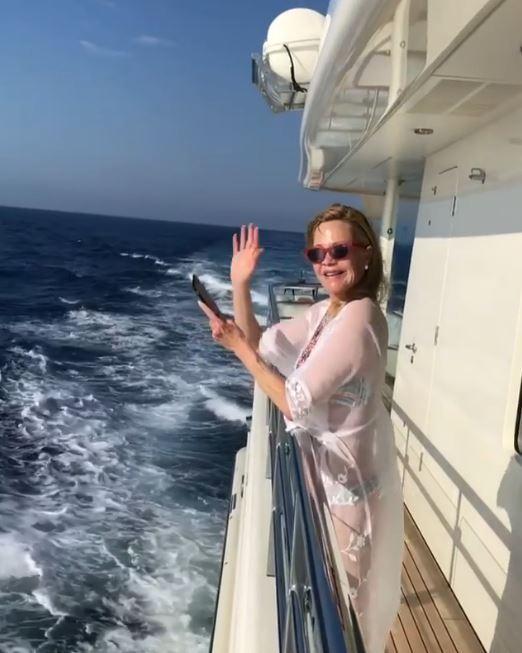 Melanie Griffith në një barkë në Korsikë  tregon format me një pelerinë trasparente