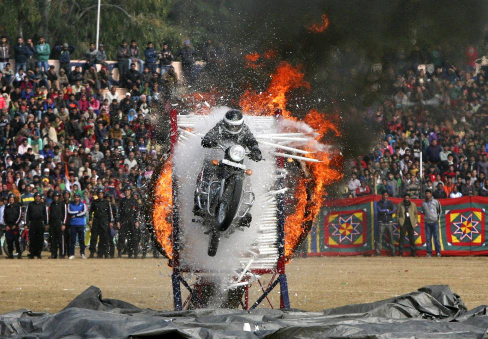 Indian policeman performs a stunt on motorcycle during the Republic Day parade in Jammu
