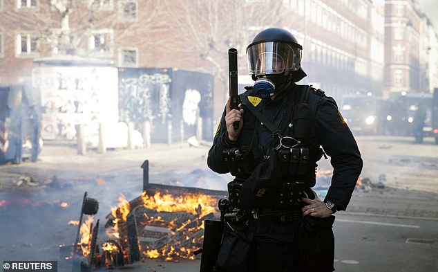 12291122 6923637 Unrest A Danish Police Officer Stands Guard With A Burning Wreck M 41 1555326218041