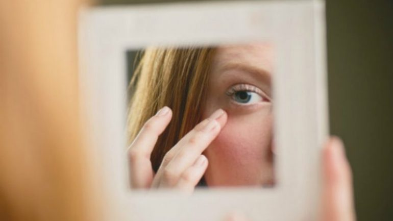 Woman Checking Under Eye Area In Mirror M 780x439